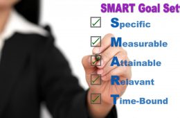 Asian business woman writing SMART Goal setting specific, measurable, attainable, relevant, time on whiteboard