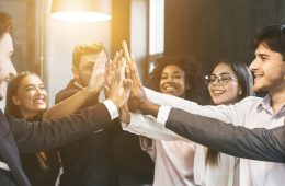 High-five for success. Diverse group of business colleagues working in office