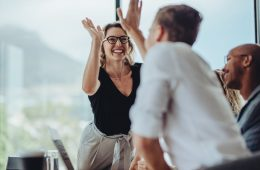 Businesswoman giving a high five to male colleague in meeting. Business professionals high five during a meeting in boardroom.
